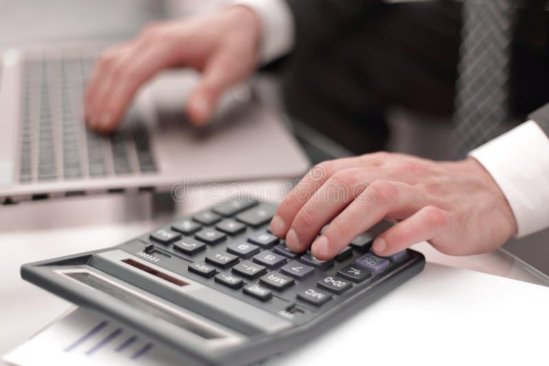 Abschluss oben Geschäftsmann macht Berechnungen auf dem Taschenrechner lizenzfreie stockfotos
