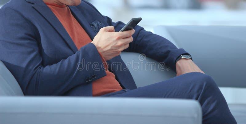 Abschluss oben Geschäftsmann unter Verwendung des Handys, der in der Lobby sitzt stockbild