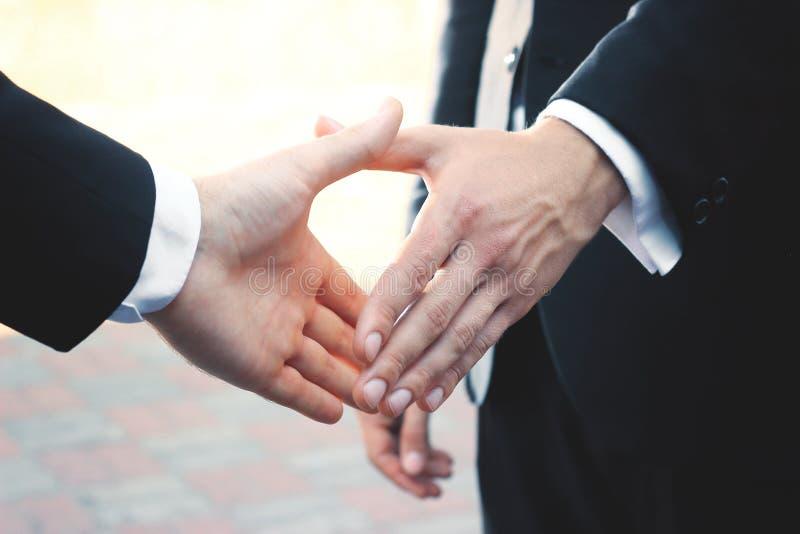 Abschluss oben Geschäftsmann zwei, der heraus Hand für Händedruck hält lizenzfreies stockbild