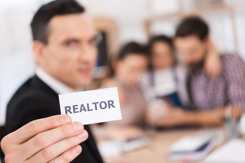 Abschluss oben Grundstücksmakler hält in der Hand weiße Karte mit Aufschrift durch Grundstücksmakler, mit Familie, die Haus kauft stockbilder