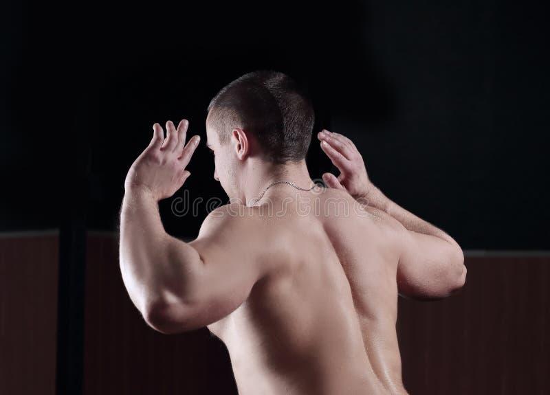 Abschluss oben Hintere Ansicht ein männlicher Bodybuilder führt eine Übung durch lizenzfreie stockbilder