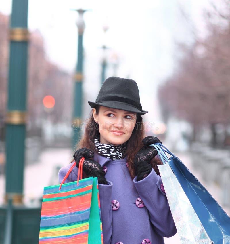 Abschluss oben junge Frau mit Einkaufstaschen auf dem Hintergrund der Stadt stockbilder