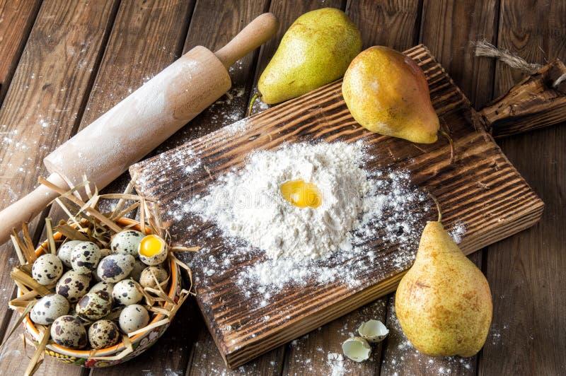 Abschluss oben Kochen von Ostern-Kuchen Gelbes Eigelb in einem Hügel des Weißmehls, umgeben durch reife große Birnen stockfoto