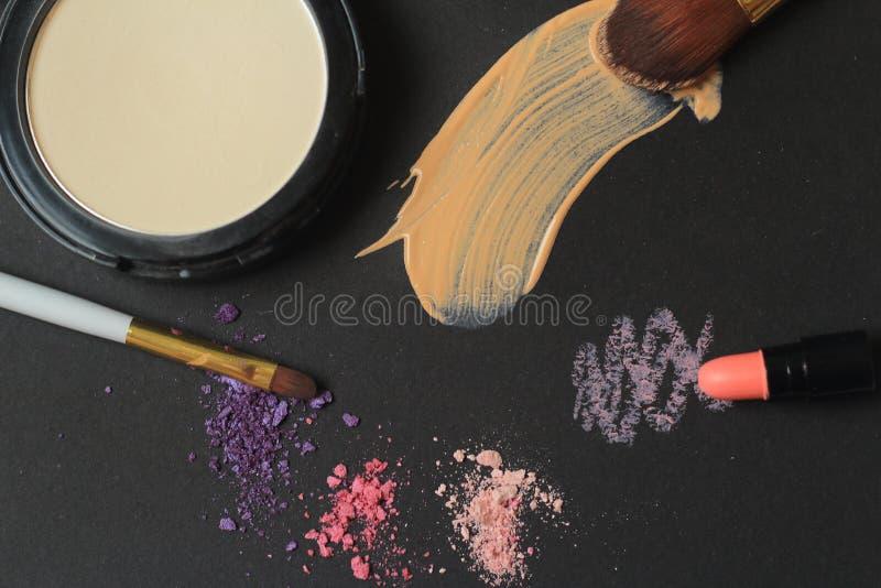 Abschluss oben Make-upbürsten, Pulver und Cremeanschläge auf schwarzem Hintergrund lizenzfreie stockfotografie