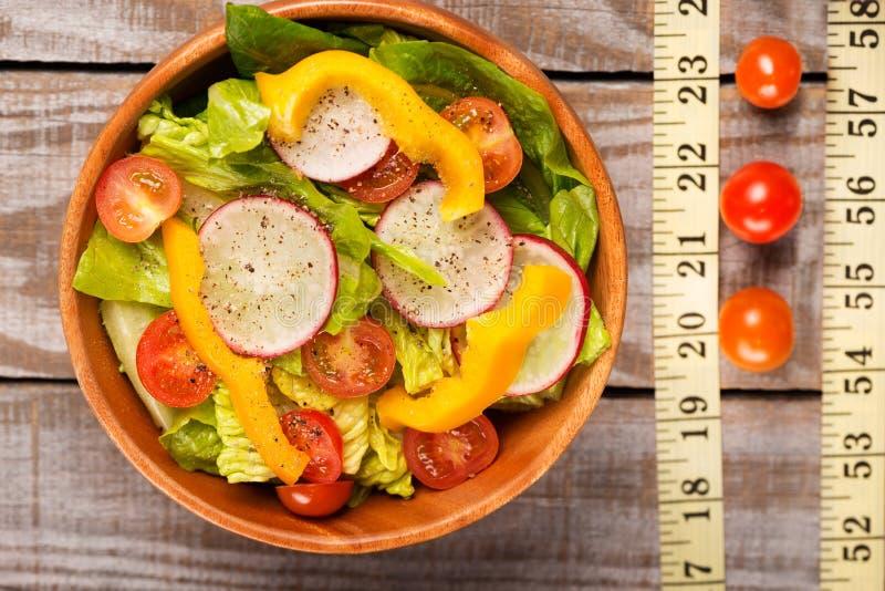 Abschluss oben mit Salat auf Holztisch mit messendem Band auf hölzernem Hintergrund stockfotografie