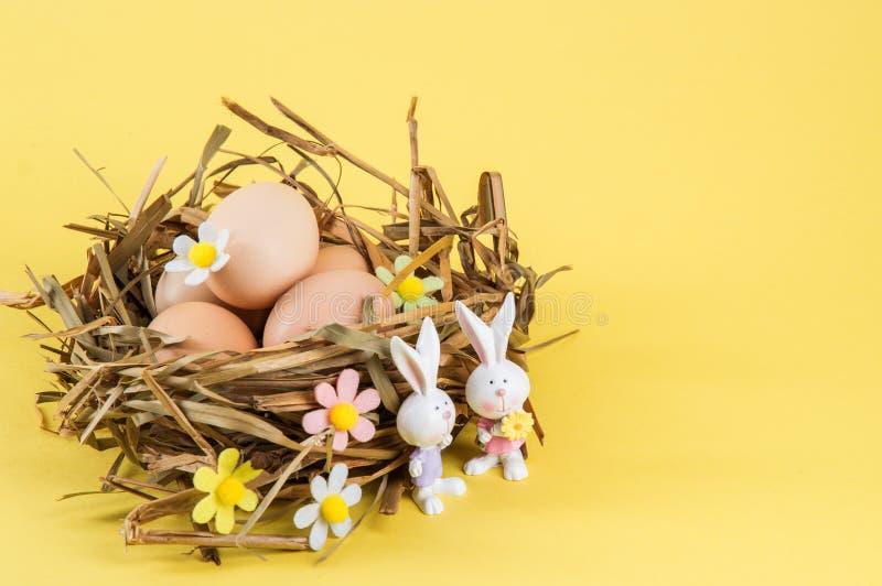 Abschluss oben Ostern-noch Leben Landeien in einem Nest des Strohs Zwei nette Porzellanh?schen im Vordergrund Gelber Hintergrund  stockbild