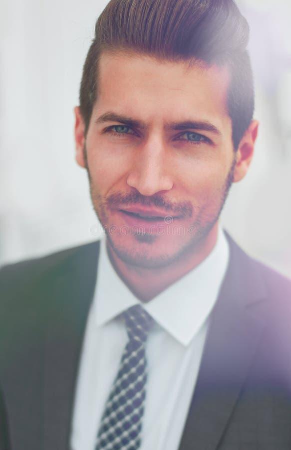 Abschluss oben Porträt eines erfolgreichen Geschäftsmannes auf dem Hintergrund des Büros stockfotografie