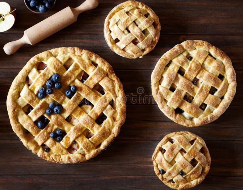 Abschluss oben Selbst gemachte Gebäckapfelkuchen-Tortenbäckerei auf dunklem hölzernem Küchentisch mit Rosinen, Blaubeere und Äpfe lizenzfreie stockbilder