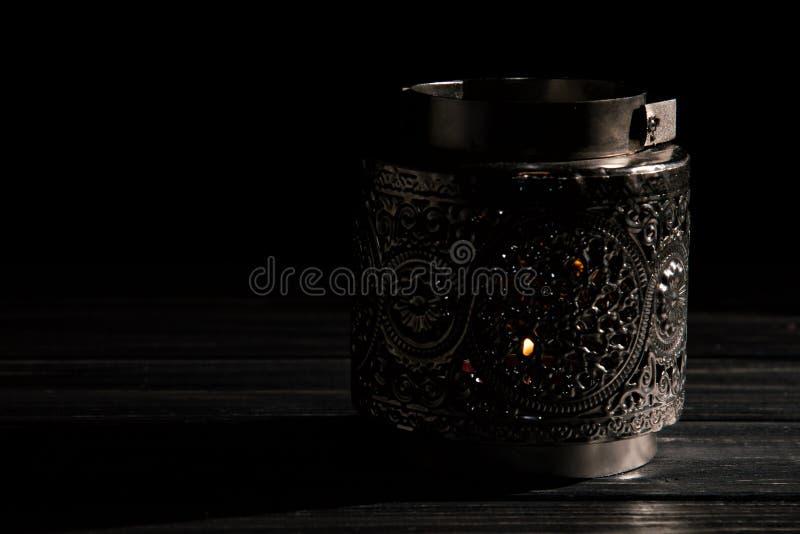 Abschluss oben Silberner Kerzenständer der Weinlese mit brennender Kerze Betrachten der Kamera Schwarzer Hintergrund Kopieren Sie lizenzfreie stockfotografie