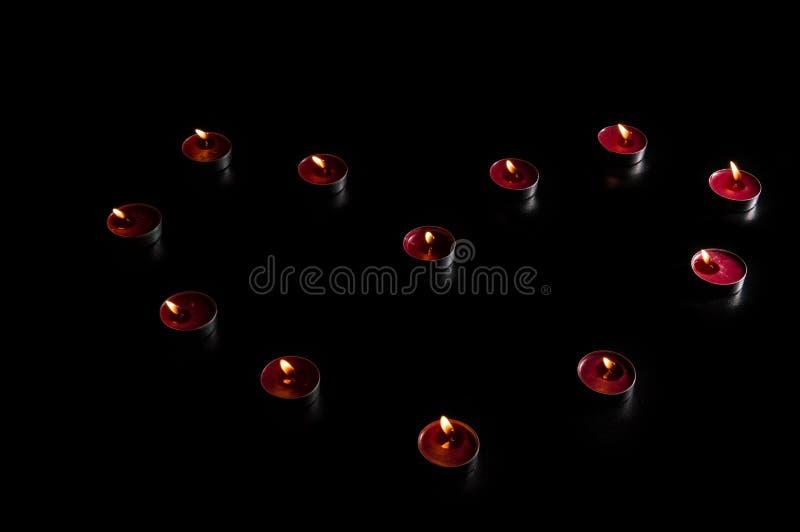 Abschluss oben Valentinsgruß ` s Tagesfeier Rote brennende Kerzen ausgebreitet in Form eines Herzens Schwarzer Hintergrund, zurüc stockfotos