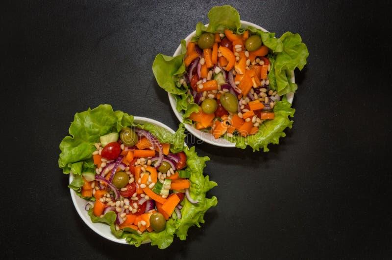 Abschluss oben Vegetarische Nahrung Zwei Schüsseln Gemüsesalat mit Tofu- und Kiefernnüssen Schwarzer Hintergrund Kopieren Sie Pla lizenzfreie stockfotografie