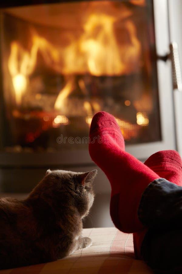 Abschluss oben von bemannt die Füße, die durch Katze Firewith sich entspannen stockfotografie