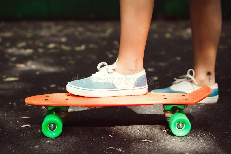 Abschluss oben von Füßen Mädchenturnschuhen fährt auf orange Penny stockfoto