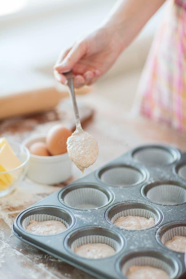 Abschluss oben von Handfüllenden Muffins formt mit Teig stockfoto
