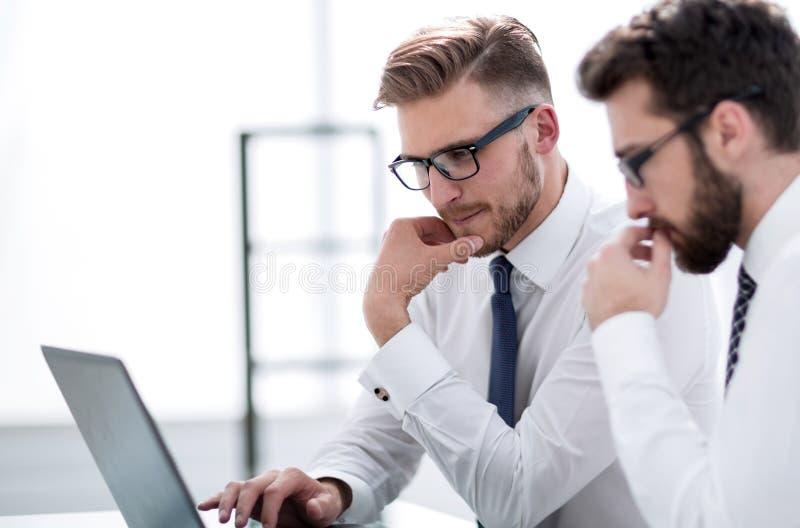 Abschluss oben zwei Angestellte benutzen einen Laptop beim Sitzen an ihrem Schreibtisch lizenzfreie stockfotos