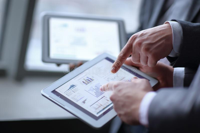 Abschluss oben zwei Geschäftsmänner, die Finanzdaten unter Verwendung einer digitalen Tablette besprechen lizenzfreie stockbilder