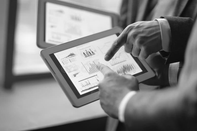 Abschluss oben zwei Geschäftsmänner, die Finanzdaten unter Verwendung eines digi besprechen lizenzfreie stockfotos