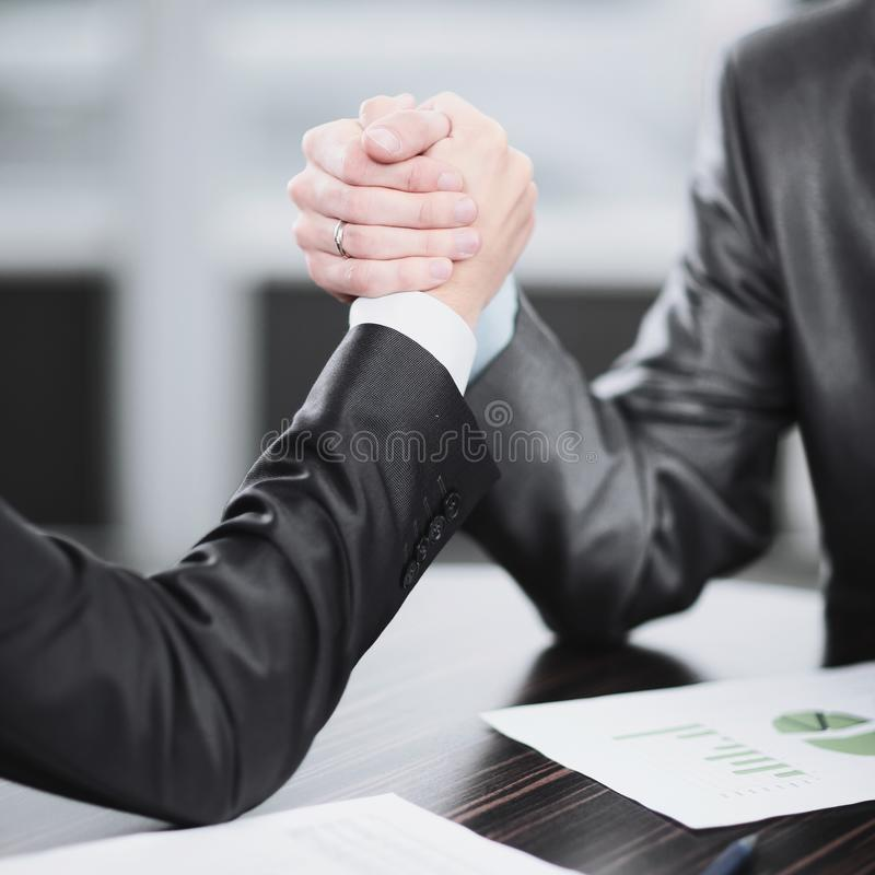 Abschluss oben zwei Geschäftsmänner nehmen an Armdrücken an einem Schreibtisch teil lizenzfreies stockfoto