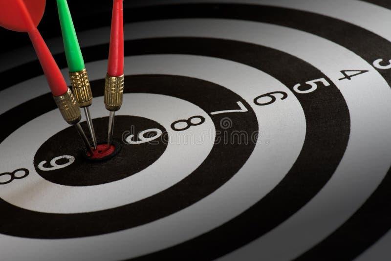 Abschluss schoss oben rote und grüne Pfeilpfeile auf Mitte der Dartscheibe, Metapher, um Erfolg und Siegerkonzept anzuvisieren lizenzfreies stockfoto