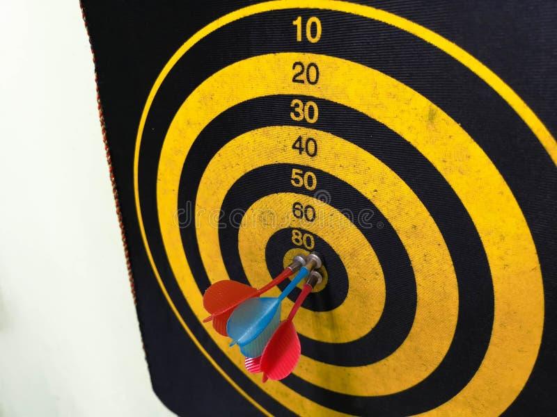 Abschluss schoss oben von einer Dartscheibe Pfeilpfeil, der das Ziel auf einer Dartscheibe w?hrend des Spiels verfehlt Pfeilgelb stockbild