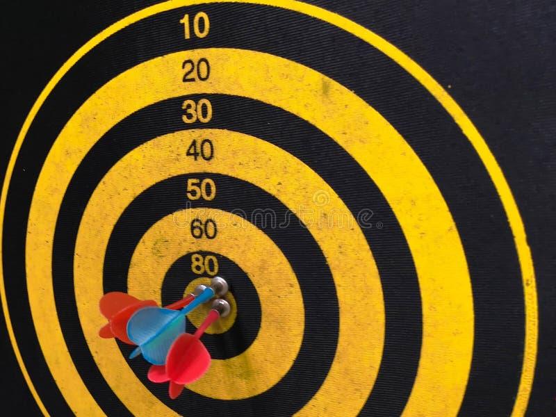 Abschluss schoss oben von einer Dartscheibe Pfeilpfeil, der das Ziel auf einer Dartscheibe w?hrend des Spiels verfehlt Pfeilgelb lizenzfreie stockfotos
