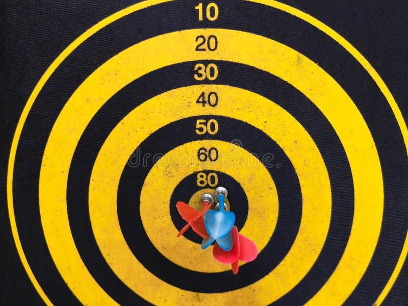 Abschluss schoss oben von einer Dartscheibe Pfeilpfeil, der das Ziel auf einer Dartscheibe w?hrend des Spiels verfehlt Pfeilgelb lizenzfreie stockfotografie