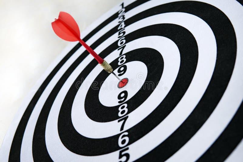 Abschluss schoss oben von einer Dartscheibe Pfeilpfeil, der das Ziel auf einer Dartscheibe w?hrend des Spiels verfehlt stockbild