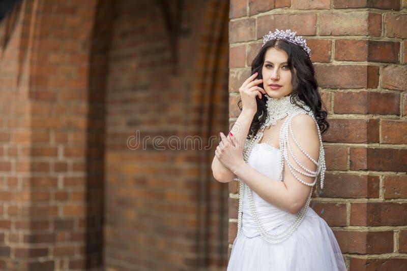 Abschlussporträt der romantischen sensual-kaukasischen Braut mit Kronen- und Ketten-Posen gegen alte Mauern Außendoos stockfotos