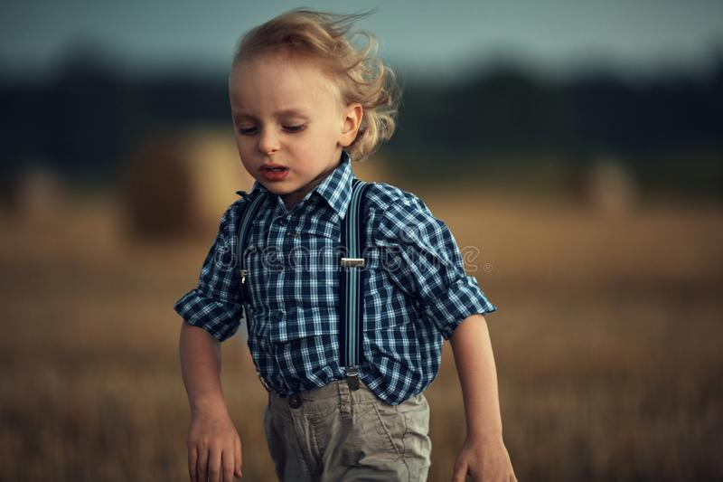 Abschlussporträt eines kleinen blonden Jungen, der auf dem Weizenfeld läuft lizenzfreies stockbild