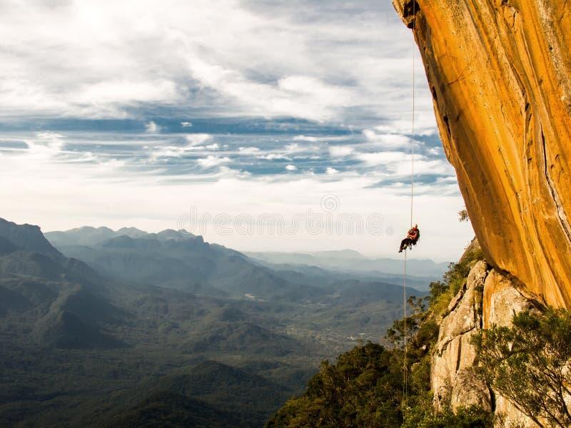 Abseiling ένας αρνητικός κίτρινος τοίχος βράχου με τα βουνά στο backgrou μετά από την αναρρίχηση βράχου στοκ εικόνα