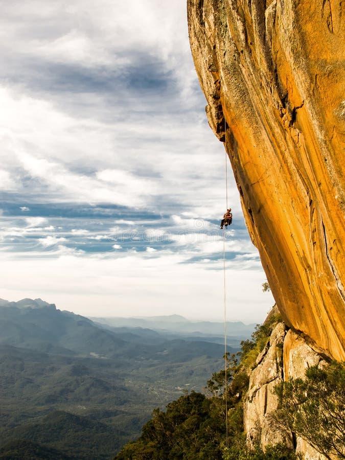 Abseiling negatywna kolor żółty skały ściana z górami na backgrou zdjęcie royalty free