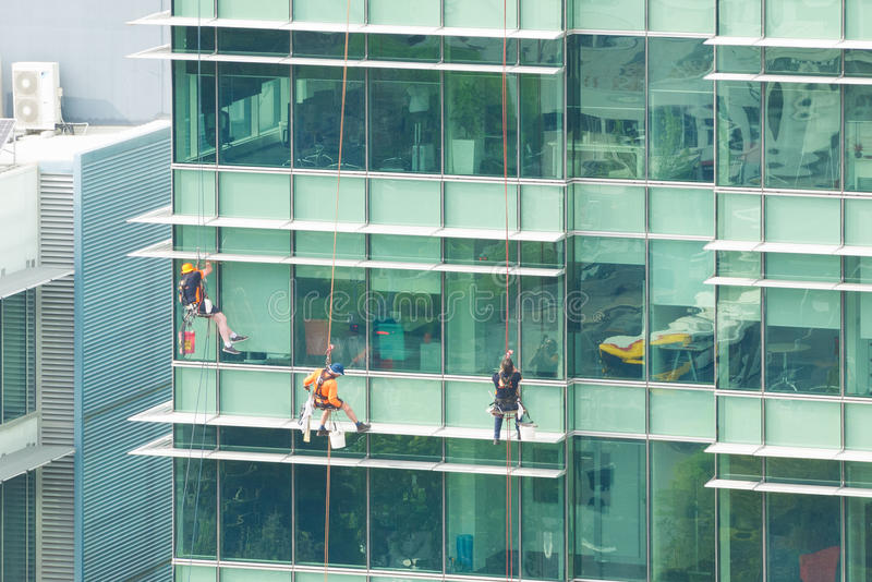Abseiling window cleaners work on office building stock photo