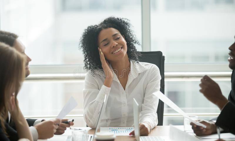 Absent-minded distracted black businesswoman dreaming smiling at stock photography