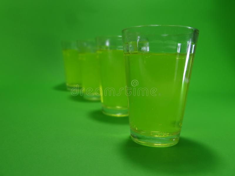 Absinthein a transparent glass on a green background. Liquour called absent on a transparent glass on a green background stock images