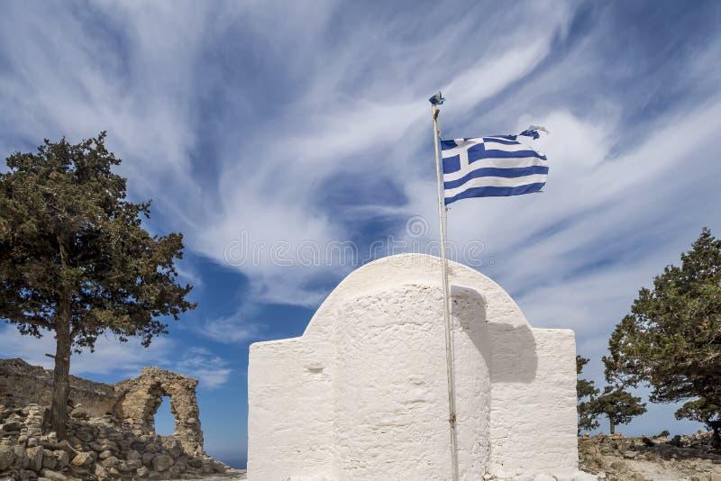 A abside de uma igreja grega típica com a bandeira no vento entre as ruínas do castelo medieval Monolithos, o Rodes, Grécia fotografia de stock
