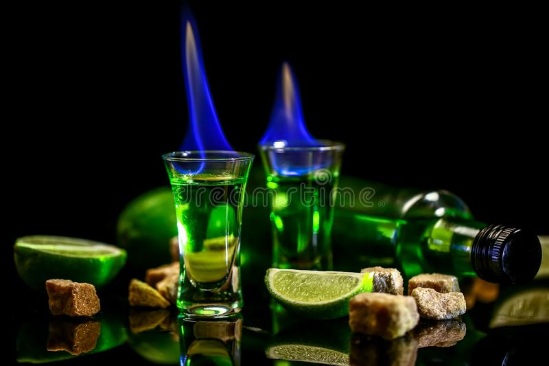Absinthe in glass with lime slices on dark background. Bottle of absinthe and glasses with burning. cube brown sugar. free space stock photos