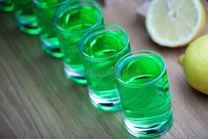 Absinthe shot glass sugar lemon wooden table stock photo