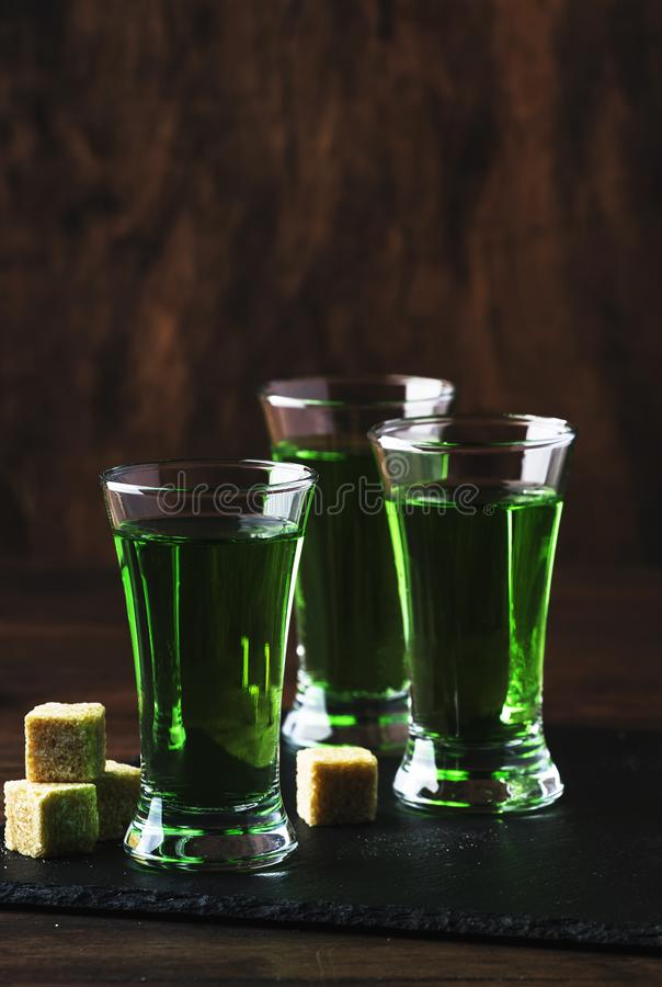 Absinthe - strong alcoholic drink, green bitter wormwood tincture in glasses on the old wooden table, place for text. Absinthe - strong alcoholic drink, green stock photos