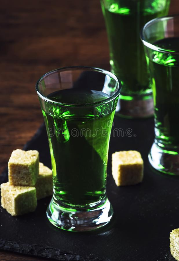 Absinthe - strong alcoholic drink, green bitter wormwood tincture in glasses on the old wooden table, place for text. Absinthe - strong alcoholic drink, green stock photography