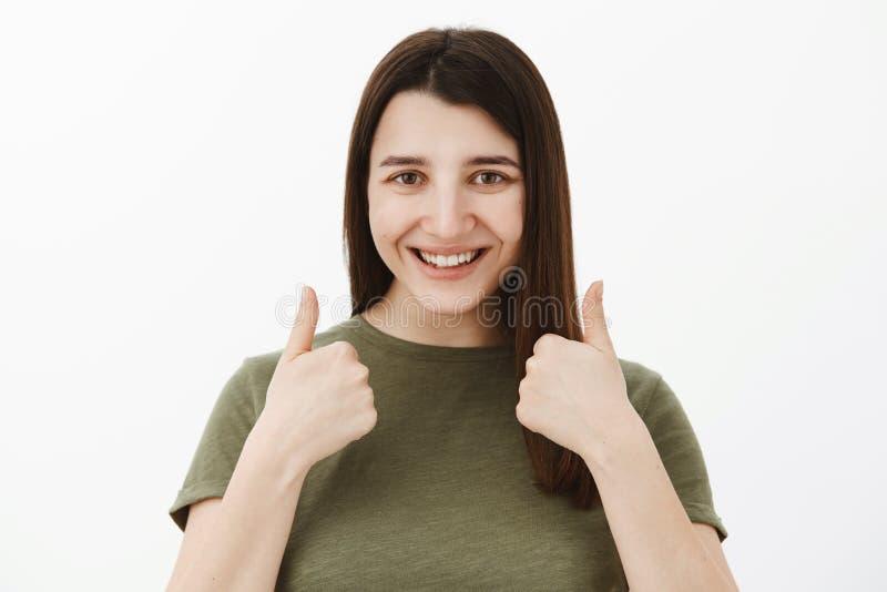 Absolutamente certo você para gostar d Cliente fêmea satisfeito optimstic seguro e amigável que mostra os polegares acima dentro fotografia de stock