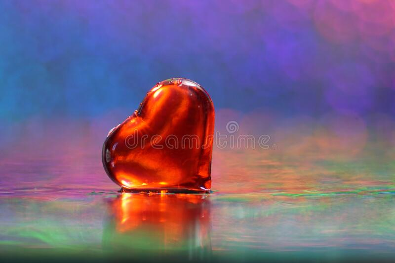 Absolutely awesome luminous red heart on a rainbow colors background royalty free stock photos
