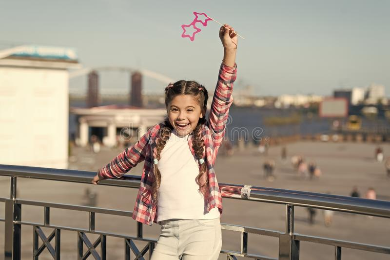 Absolutely thrilled. Happy party girl on urban background. Adorable girl holding prop glasses for party fun. Cute small stock photography