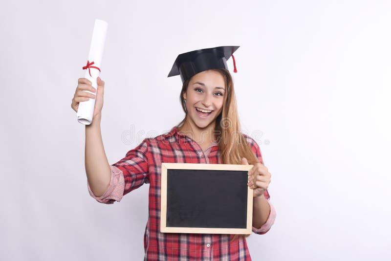 Absolvent des jungen Mädchens mit Tafel und Diplom stockfoto