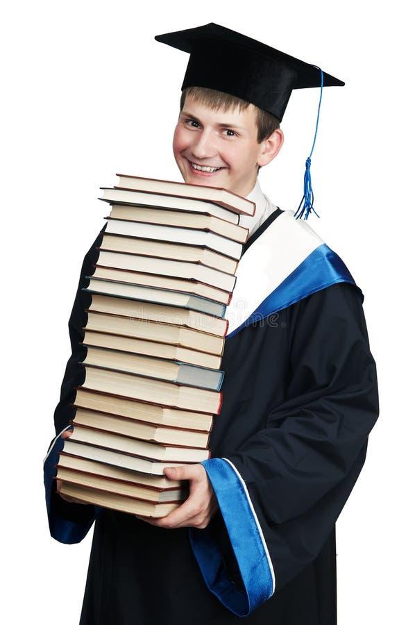 Absolvent im Kleid mit Büchern lizenzfreie stockfotos