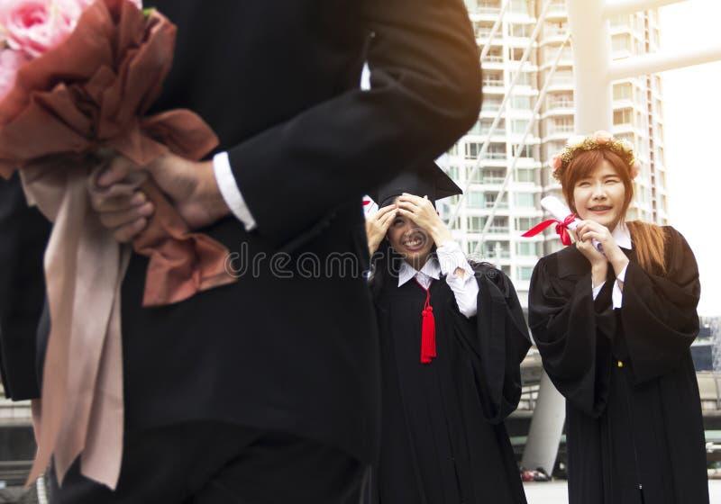 Absolwentów absolwentów kobiety uśmiech i jest szczęśliwy po skalowania zdjęcia stock