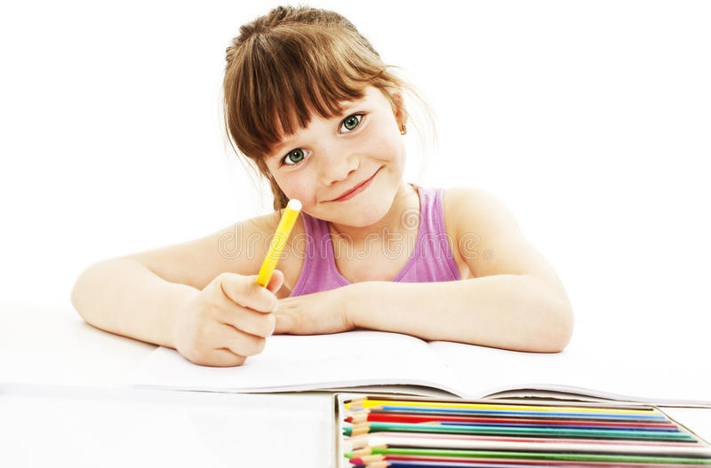 Absorbed little girl drawing with colorful pencils royalty free stock photography