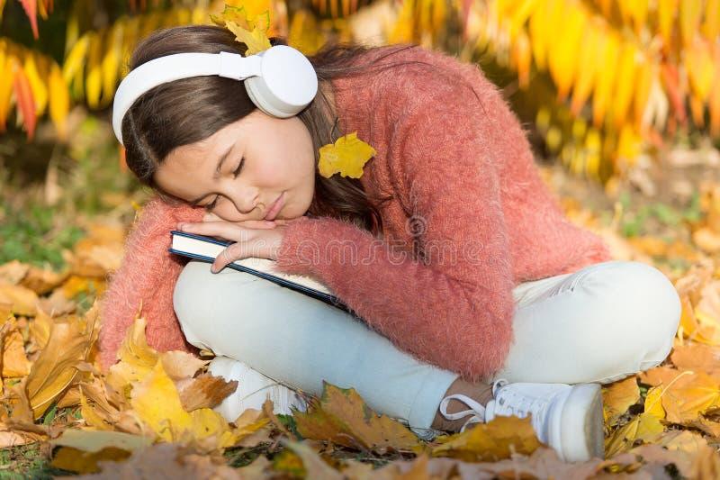 Absorber libro mientras duerme Un niño pequeño se quedó dormido escuchando un libro en línea Niña pequeña disfruta aprender en lí fotografía de archivo
