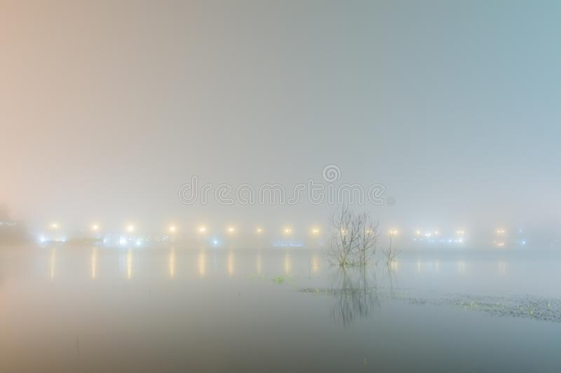 Abstact blurred background of Uttamanusorn Bridge or Mon Bridge. With light reflection on river in the evening at Sangkhlaburi district,Kanchanaburi province stock photography