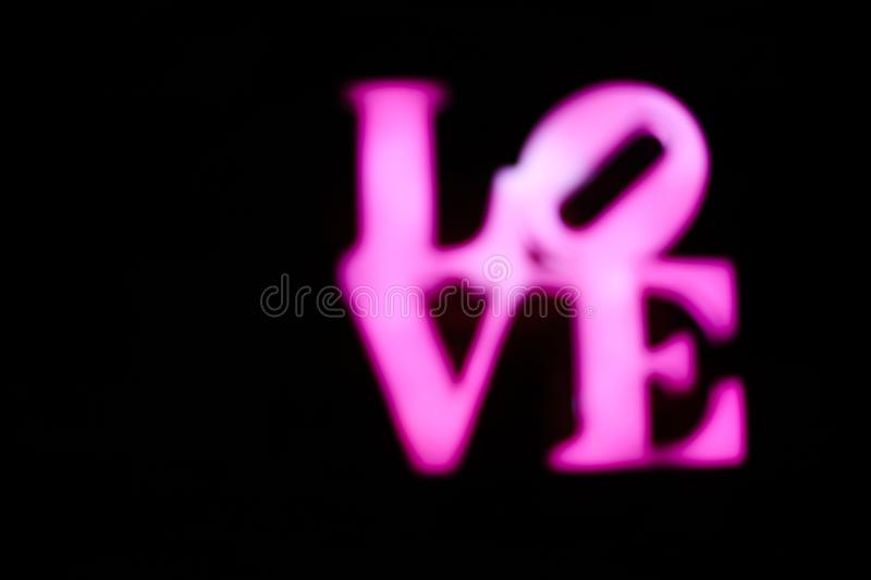 Abstact blurred Plastic pink sign of word LOVE on black background. stock photography