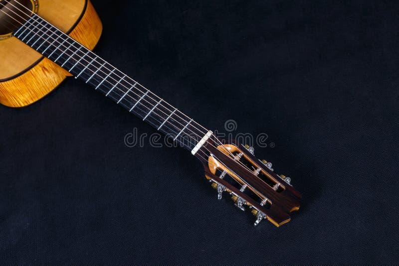 Abstimmende Klammern auf hölzerner Mechanik von sechs Akustikgitarrehals der Schnüre auf schwarzem Hintergrund lizenzfreies stockbild